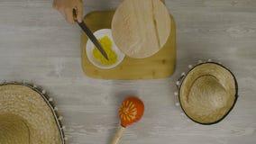 Setzt Lebensmittel in den Teller mit einem Messer ein Ist auf dem Tisch die zwei mexikanischen Hüte, maracas, Abstraktion für ins Stockfoto