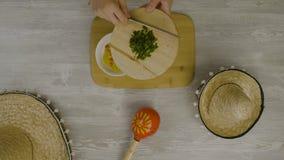 Setzt Lebensmittel in den Teller mit einem Messer ein Ist auf dem Tisch die zwei mexikanischen Hüte, maracas, Abstraktion für ins Stockfotos