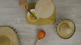 Setzt Lebensmittel in den Teller mit einem Messer ein Ist auf dem Tisch die zwei mexikanischen Hüte, maracas, Abstraktion für ins Stockbild