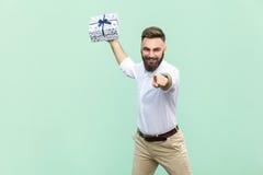 Seu para você! Homem de negócios adulto novo, guardando a caixa de presente, apontando o dedo na câmera e no sorriso toothy Isola Imagens de Stock Royalty Free