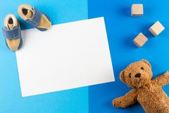 Seu um menino, um fundo azul da festa do bebê do tema ou do berçário com cartão vazio, um besr da peluche, uns blocos de madeira  imagens de stock