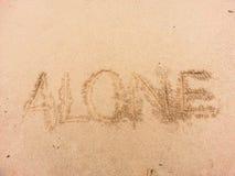 Seul écrit sur le sable par la mer Images libres de droits