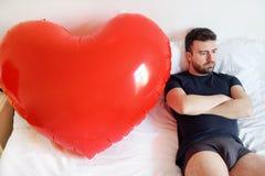 Seul amour de recherche d'homme se reposant sur le lit Image stock
