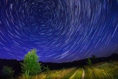 Seul arbre sur le ciel nocturne avec des étoiles, des startrails et la route de campagne Photos stock