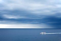 Seul bateau blanc sur la mer et le ciel orageux images libres de droits