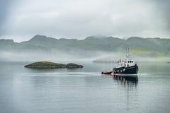 Seul bateau conduisant en mer brumeuse dans les montagnes écossaises photos libres de droits