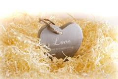 Seul coeur en bois brun d'amour dans un nid d'amour Photo stock