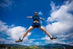Seul homme sautant pour la joie sur une colline d'herbe au-dessus de ligne d'horizon Images libres de droits
