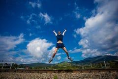 Seul homme sautant pour la joie sur une colline d'herbe au-dessus de ligne d'horizon Photographie stock