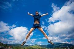 Seul homme sautant pour la joie sur une colline d'herbe au-dessus de ligne d'horizon Image stock