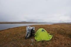 Seul voyageur de moto près de tente verte au rivage foncé de steppe de brouillard de tristesse du lac photographie stock