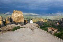 Seule femelle dans le plaid blanc au bord du regard de roche sur les monastères de Meteora Femelle sur la roche et les monastères Images libres de droits