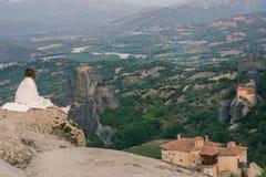 Seule femelle dans le plaid blanc au bord du regard de roche sur les monastères de Meteora Femelle sur la roche et les monastères Photos stock