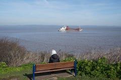 Seule femme assise par la mer Photographie stock libre de droits