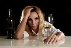 Seule femme blonde alcoolique ivre dans le regard déprimé gaspillé réfléchi au verre de vin blanc Image stock
