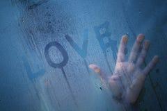 Seule femme dans l'amour à la fenêtre pluvieuse Photos stock