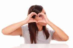 Seule femme latine regardant par le signe d'amour Photo libre de droits