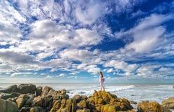 Seule jeune femme seul se tenant sur le regard de roche volcanique sur l'horizon Photos libres de droits