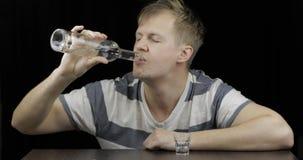 Seule vodka potable d'homme d?prim? dans une chambre noire Concept d'alcoolisme photos stock