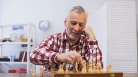 Seuls échecs de jeu masculins pluss âgé et regardant à la caméra se préparant à la concurrence banque de vidéos