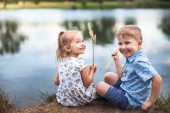 Seus crianças, menina e menino felizes estão sentando-se perto do lago foto de stock