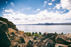 Sevan lake and white clouds blue sky on a sunny day, Armenia. The view on mountains from the pier of Sevan lake and white clouds on blue sky on a sunny day stock photography
