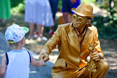 Sevastopol, Russian Federation-26 of July, 2015: Street artist d. Ressed as a gold statue takes up an position,in honor of a holiday of navy of Russia Royalty Free Stock Image