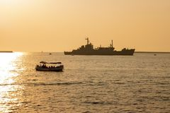 Sevastopol, Ukraine - July 30, 2011: The military ship. General Ryabikov in the sea. Near the boat floats with tourists. Horizontally framed shot Royalty Free Stock Photo