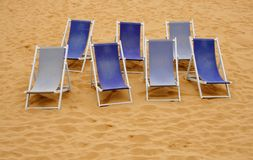 Seven beach chairs. Seven blue beach chairs in the sand Stock Images