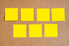 Seven black yellow sticky notes on brown wood board Royalty Free Stock Photo