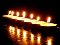 Seven candles. Line of ardent candles in darkness with reflexes Royalty Free Stock Photography