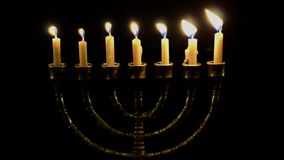 Seven candles in menorah. Seven burning candles in menorah. Black background stock footage