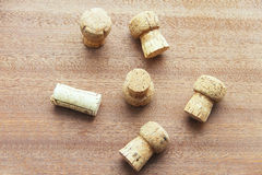 Seven caps of cork champagne randomly scattered on a wooden board Royalty Free Stock Photos