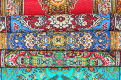 Seven carpets lie in rouleau on each other Stock Images