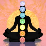 Seven chakra symbols column on black human being by sunset - 3D render Royalty Free Stock Photos