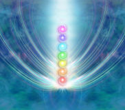 The Seven Chakras. Ethereal blue energy formation background with a central column of the seven chakras in a beam of spiraling light Stock Illustration