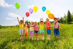 Seven children with balloons in green field Royalty Free Stock Photography