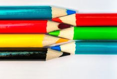 Seven colored pencils. The colors red, green, blue, cyan, magenta, yellow and black. Concept of color profiles converting from RGB. To CMYK stock photo