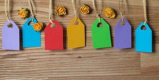 Seven colorful tags for text and paper flowers on wood.