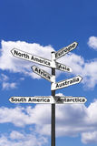 Seven continents signpost vertical. Signpost with arrows pointing to the seven continents of the world against a blue cloudy sky stock images