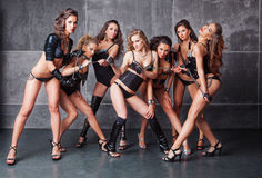Seven Cute go-go sexy girls in black with diamonds. Costume pulling a chain Stock Images
