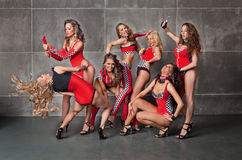 Seven Cute go-go sexy girls in red racing costume. In garage Royalty Free Stock Photo