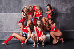 Seven Cute go-go sexy girls in red racing costume. Having fun Royalty Free Stock Image
