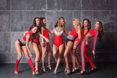 Seven Cute go-go sexy girls in red racing costume. Having fun Stock Images
