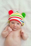 Seven days old baby with a colorful strips hat in a bed Royalty Free Stock Image