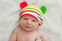 Seven days old baby with a colorful strips hat in a bed Stock Images