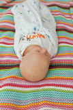 Seven days old baby swaddle with bamboo blankets with stars pattern and a colorful background in a bed Stock Photos