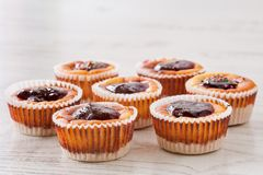Seven delicious, homemade mini cheesecakes with berry jam in muffin cups on a wooden table royalty free stock photos