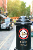 A Seven Dials bollard and a blurred classic black cab in London. Royalty Free Stock Images