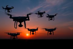 Silhouette of drones in the sky, orange sunset stock photo